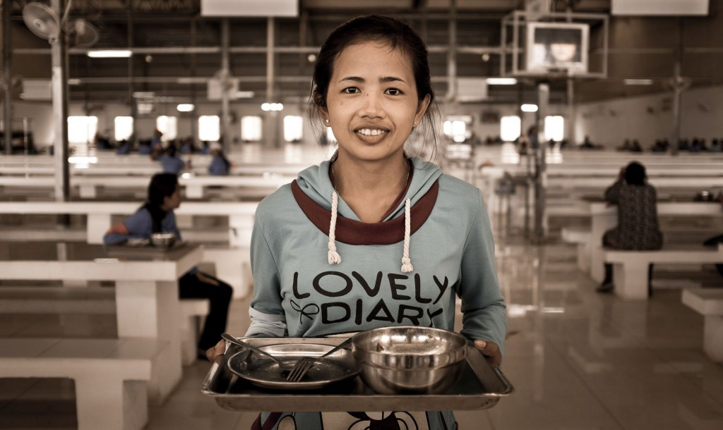 A female garment worker receiving foods from their factory, Cambodia. Photo by ILO (Asia-Pacific), uploaded on 14 July 2015. Creative Commons Attribution-NonCommercial-NoDerivs 3.0 IGO