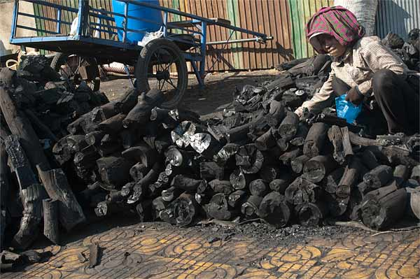 Woman sorting charcoal in Phnom Pehn. Photo by Kelly Irving, taken on 25 February 2010. Licensed under Creative Commons Attribution-NoDerivs 2.0 Generic.