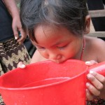 Young child drinks clean water in Cambodia. Photo by Cecilia Snyder, taken on 12 July 2003. Licensed under  CC BY-NC-ND 2.0
