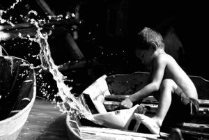 Kid scooping water off a boat - Edwin Lee - December 8 2008 – Licensed under CC BY-SA 2.0.