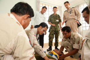 Japanese military members observe as Cambodian sailors attach a neck brace to a patient during a Pacific Partnership knowledge exchange in Sihanoukville, Cambodia.