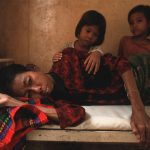 Two daughters look at their mother who is dying from HIV/AIDS. Cambodia. 2002.